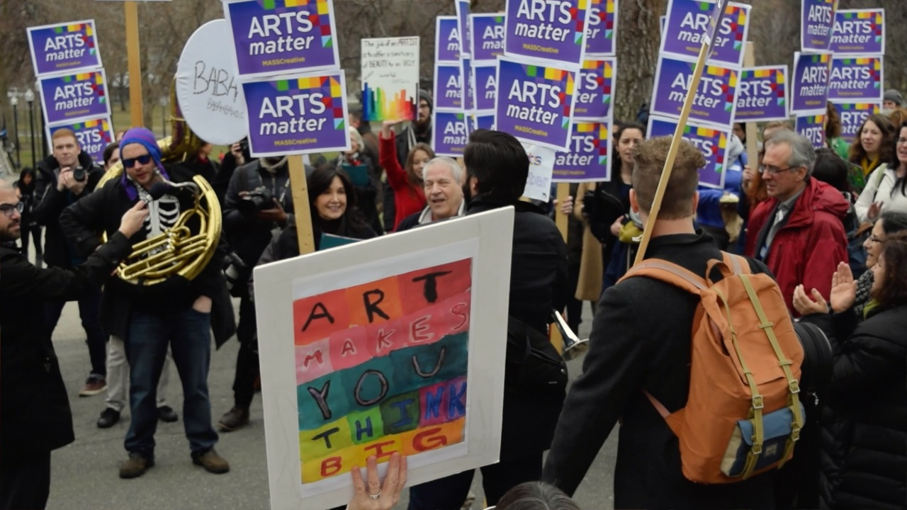 """Marcher holds a sign that reads """"Art Makes You Think Big."""""""